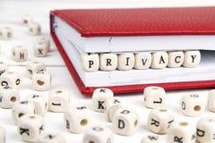 Word Privacy in houten blokken in rood notitieboekje op wit w wordt geschreven dat Stock Foto's