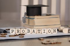 Word PROBATION composed of wooden dices. Black graduate hat and books in the background. Closeup royalty free stock photos