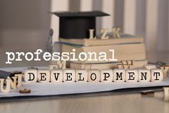 Word PROFESSIONAL DEVELOPMENT composed of wooden dices. Black graduate hat and books in the background. Closeup stock photo