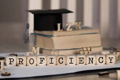 Word PROFICIENCY composed of wooden dices. Black graduate hat and books in the background. Closeup stock photo