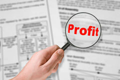 Word Profit, magnifying glass in hand Stock Photography
