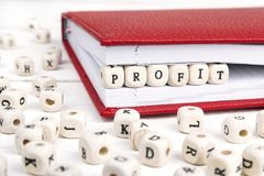 Word Profit written in wooden blocks in red notebook on white wo Royalty Free Stock Photography