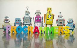 The word  PROGRAMMERS with wooden letters and retro toy robots. On an old wooden floor with reflection Stock Images