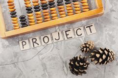Word PROJECT laid out of handwritten letters on cardboard squares near old wooden abacus and three cones. On gray cracked concrete royalty free stock photography