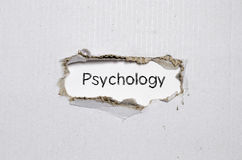 The word psychology appearing behind torn paper. Stock Photos