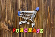 Word `purchase` and empty shopping cart on wooden background.  Stock Photo
