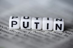 Word PUTIN formed by wood alphabet blocks on newspaper. Closeup Stock Photo