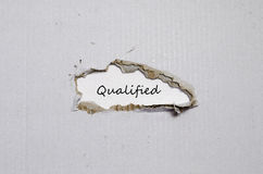 The word qualified appearing behind torn paper Stock Photo
