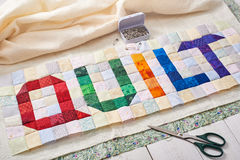 The word quilt sewn from colorful square and triangle pieces of fabric Stock Image
