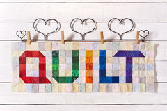 The word quilt sewn from colorful square and triangle pieces of fabric Royalty Free Stock Image