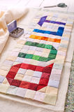 The word quilt sewn from colorful square and triangle pieces of fabric Royalty Free Stock Photo