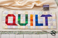 The word quilt sewn from colorful square and triangle pieces of fabric Stock Images