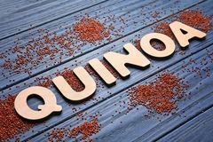 Word QUINOA made of wooden letters and seeds. On table stock images
