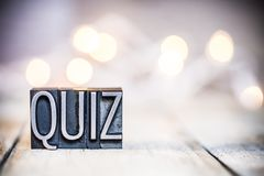 Quiz Concept Vintage Letterpress Type Theme. The word QUIZ written in vintage metal letterpress type on a bokeh light and wooden background stock photos
