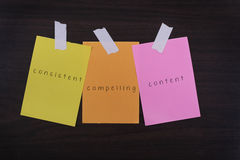 Word quotes of consistent compelling content on sticky color paper. S against wooden textured background Royalty Free Stock Image