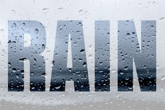Word RAIN. Double exposure word RAIN combined with image of raindrops on the glass Royalty Free Stock Photos