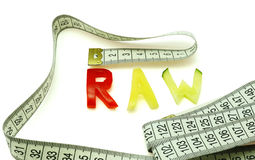 """Word raw composed of slices of different vegetables with measuring tape. Words """"raw diet"""" composed of slices of different vegetables on white  background Royalty Free Stock Photos"""