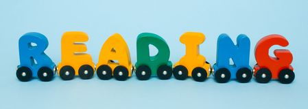 Word Reading made of letters train alphabet. Bright colors of red yellow green and blue on a white background. Early childhood dev stock photos