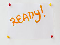 Word Ready! drawn on a sheet of paper. Word Ready! drawn with orange watercolor paint on a sheet of paper pinned up on the white wall Royalty Free Stock Photo