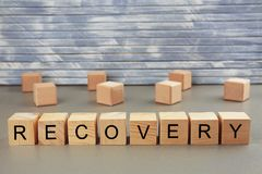 Word recovery written on wooden blocks. On wall background royalty free stock images
