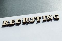 The word recruiting is written in wooden letters on a white background, the concept of hiring employees, recruitment in business. And army royalty free stock photo