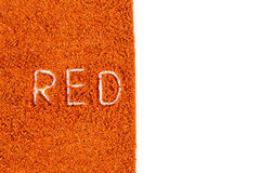 The word red written in pepper powder background Stock Image