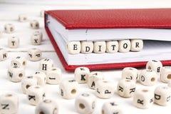 Word Redacteur in houten blokken in rood notitieboekje op witte wo wordt geschreven die Stock Foto's