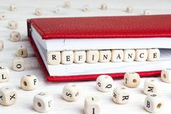 Word Refinance written in wooden blocks in red notebook on white wooden table. Wooden abc royalty free stock image