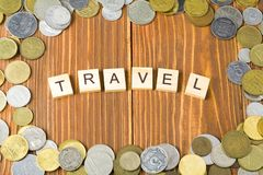 Word REIS op houten kubus met muntstukkenkader bij houten achtergrond Besparingsplannen voor reisbegroting stock afbeeldingen