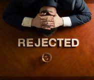 Word Rejected and devastated man composition. Word Rejected made of wooden block letters and devastated middle aged caucasian man in a black suit sitting at the royalty free stock photo