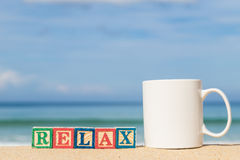 Word RELAX in colorful alphabet blocks and coffee cup on tropica Royalty Free Stock Photos