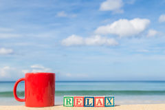 Word RELAX in colorful alphabet blocks and coffee cup on tropica Stock Images