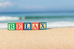 Word RELAX in colorful alphabet blocks on tropical beach Royalty Free Stock Photo