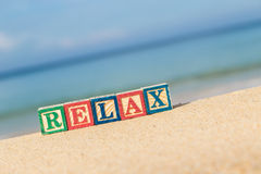 Word RELAX in colorful alphabet blocks on tropical beach Stock Image