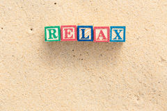 Word RELAX in colorful alphabet blocks on tropical beach Stock Photo