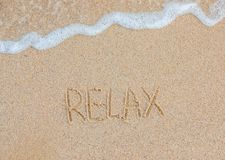 Word Relax handwritten on sandy beach. Travel concept. Summer time vacation. Word Relax handwritten on sandy beach with soft ocean wave on background. Travel royalty free stock images
