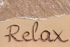 Word Relax is hand written on the beach. Word Relax is handwritten on the sandy beach Royalty Free Stock Image