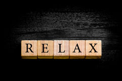 Word RELAX isolated on black background with copy space. Word RELAX. Wooden small cubes with letters isolated on black background with copy space available stock image