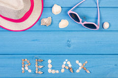 Word relax made of seashells, sunglasses and straw hat on blue boards, summer time, copy space for text Stock Image