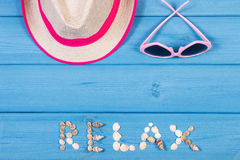 Word relax made of seashells, sunglasses and straw hat on blue boards, summer time, copy space for text Stock Photography