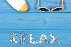 Word relax made of seashells, sunglasses and sun lotion on blue boards, summer time, copy space for text Stock Photo