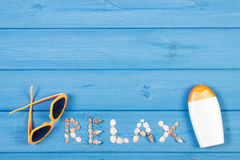 Word relax made of seashells, sunglasses and sun lotion on blue boards, summer time, copy space for text Royalty Free Stock Photography