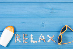 Word relax made of seashells, sunglasses and sun lotion on blue boards, summer time, copy space for text Royalty Free Stock Photo