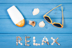 Word relax made of seashells, sunglasses and sun lotion on blue boards, summer time Stock Photo