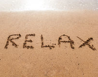 Word Relax on sand. Word Relax in handwriting on sandy beach Stock Images