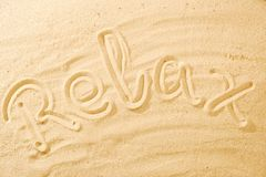 Word Relax on sand beach. Concept background idea royalty free stock images
