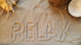 the word relax  in the sand with seashell and coconut. Stock Photography