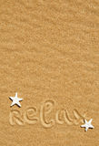 Word relax and seashells on the sand Royalty Free Stock Image