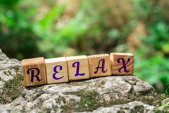 Word relax on stone. Word relax on wooden cubes on rock with green nature blur background stock photography