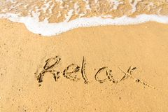 The word RELAX written into the sand. On a tropical sandy beach in paradise. The waves are just about to wash the word away stock photos